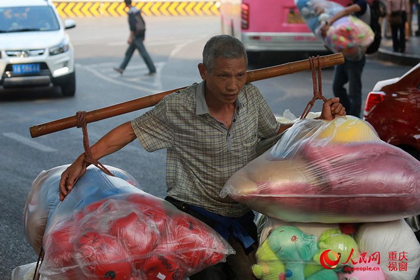 """日下午,在重庆朝天门批发市场,一名""""棒棒""""挑起顾客买好的商品图片"""