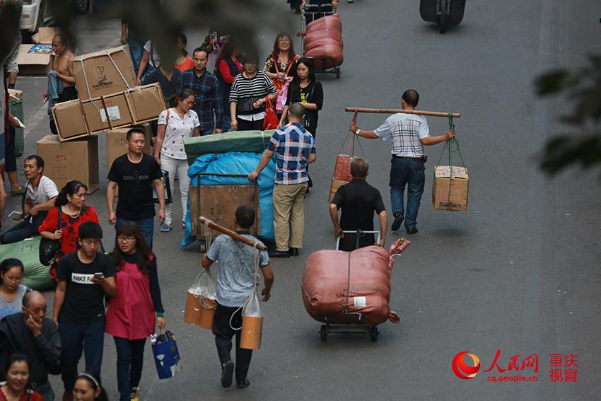 """日下午,在重庆朝天门批发市场,几名""""棒棒""""挑起顾客买好的商品图片"""