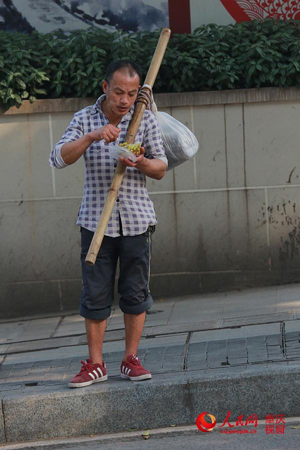 """日下午,在重庆朝天门批发市场,一名""""棒棒""""在路边吃快餐果腹.图片"""