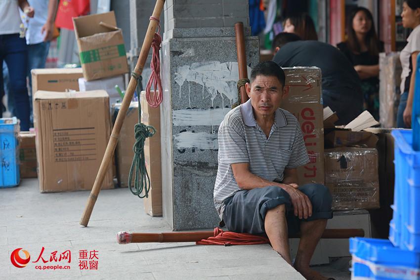"""重庆朝天门批发市场,一名""""棒棒""""在路边坐着等待业务.刘政宁 摄-图片"""