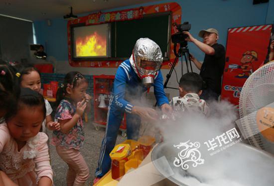 老师教孩子们使用消防面具. 记者 陈龙翔 摄