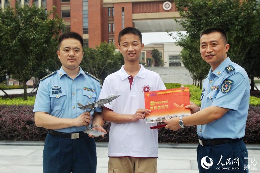 李成林从空军招飞局成都选拔中心书记杜江手中接过录取通知书.图片