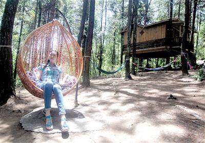 景区内的空中木屋,游客坐在木屋前的椅子上休憩.本报记者 雷键 摄