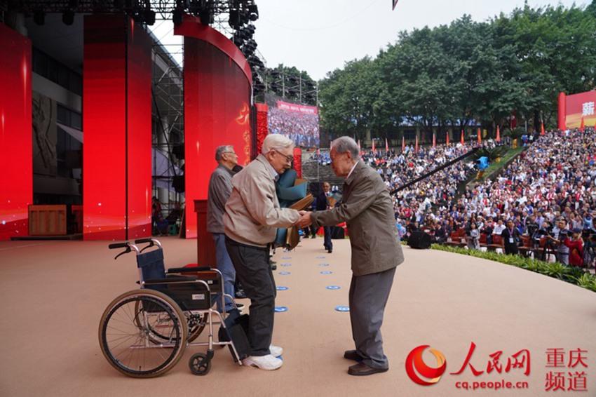 95歲高齡的學生獻花,94歲的老師堅持從輪椅上站起來接受獻花。鄒樂攝