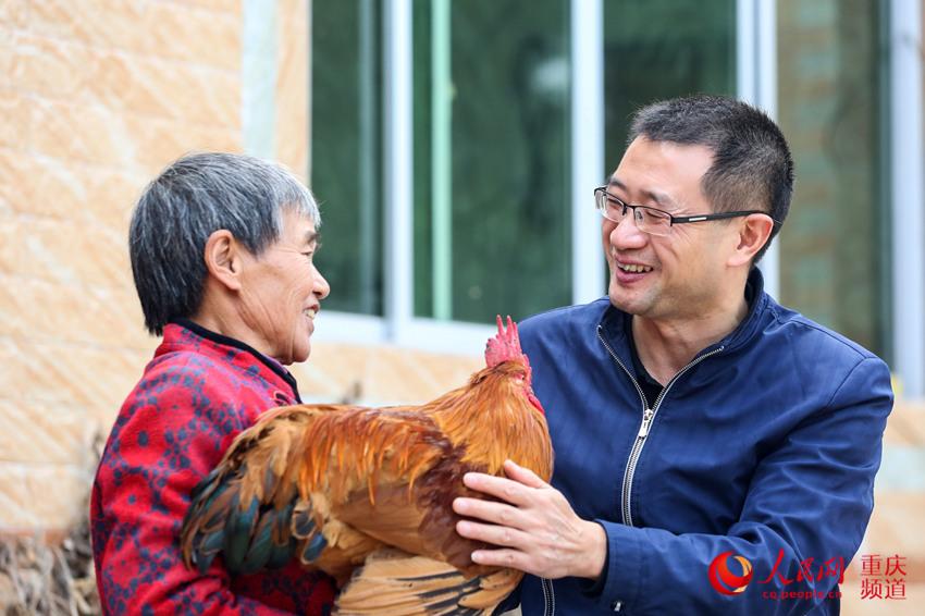 村民抱着公鸡让驻村第一书记李大军检查(右一)。何超摄