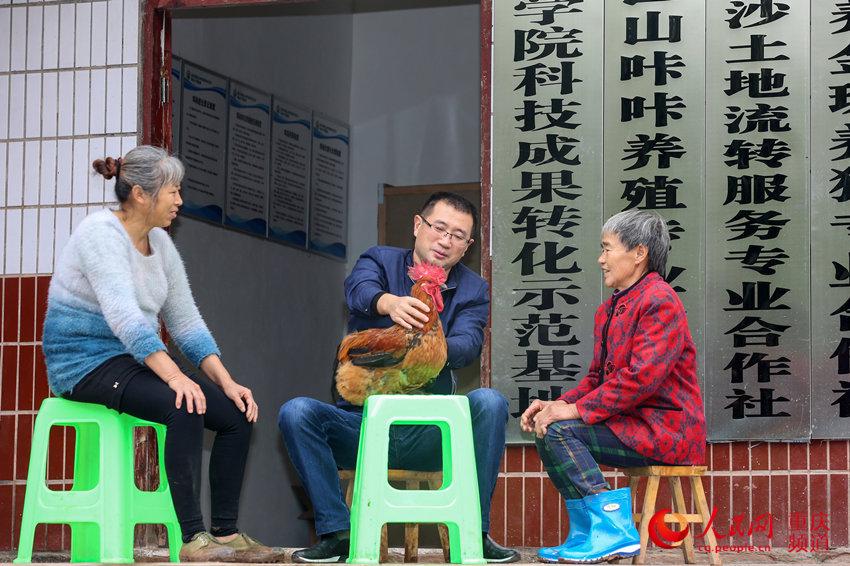 驻村第一书记李大军在检查公鸡的生长情况。何超摄