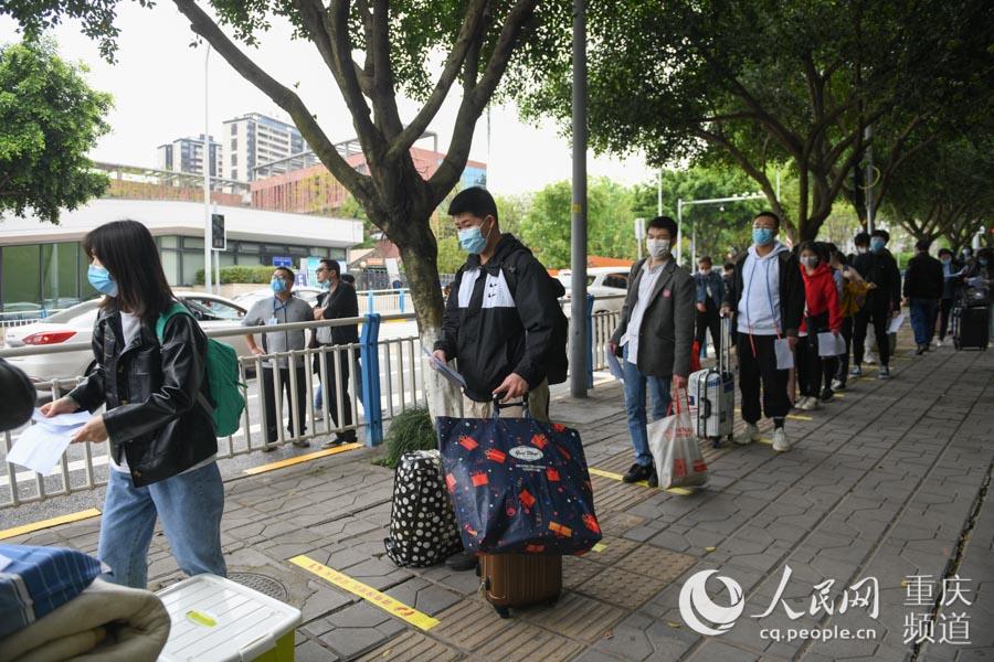 学生有序排队,等待进行入校前的体温检测。邹乐 摄