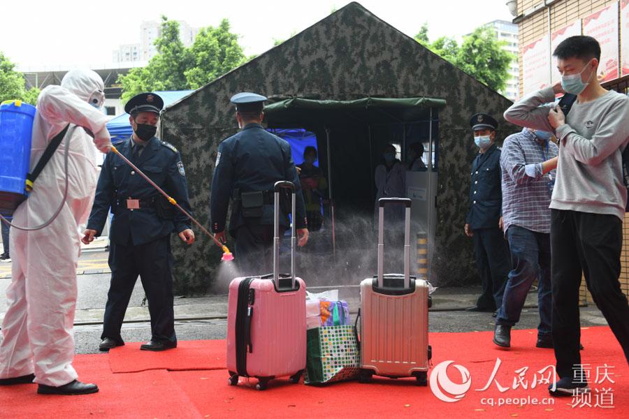 工作人员对学生行李进行消毒处理。邹乐 摄