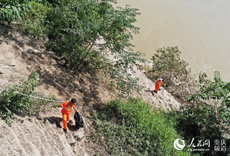 8月6日,在重庆九龙坡区谢家湾长江沿岸,环保志愿者们头顶烈日,在峭壁之上清理垃圾。